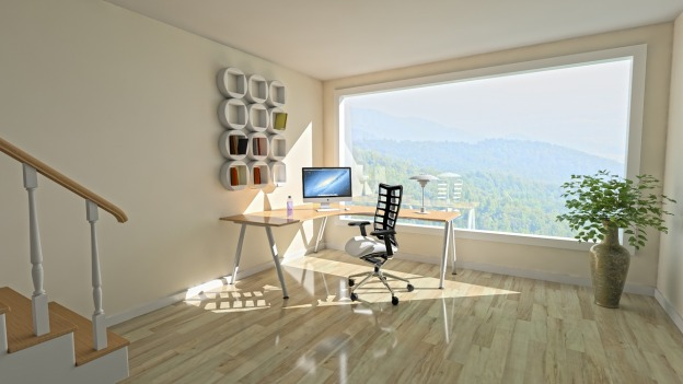 Image shows a home office that is set up next to a window in a home overlooking a forest. The home office is an l shaped desk with an ergonomic chair, table lamp, water bottle, mouse and a circle wall display that multitasks as art and space to hold home office documents and supplies.