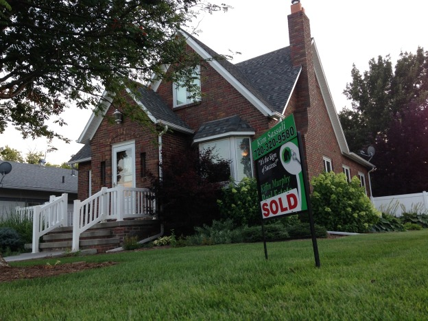 Image shows a tudor style brick house with a sold realtor sign in front of it.