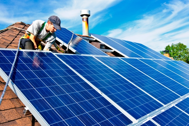 Image shows a man installing solar panels to the roof of a residential building.